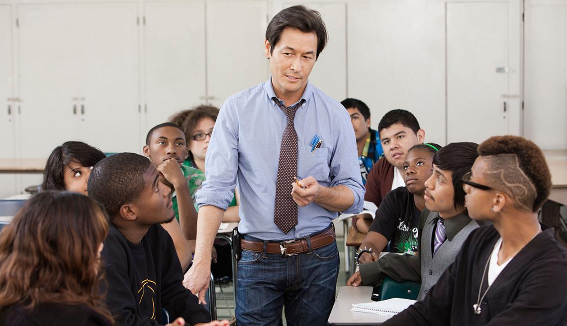 Profesor en medio de un grupo de estudiantes universitarios como uno de los trabajos donde buscan personal