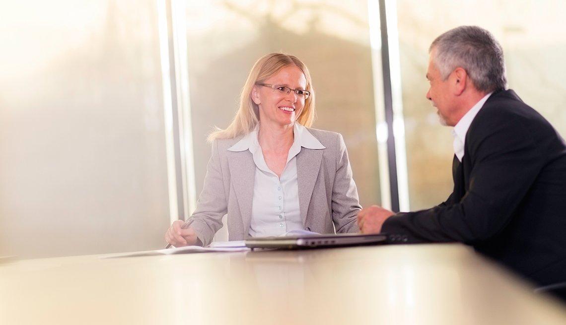 Mujer recibiendo la asesoría de un hombre en una sala de juntas.