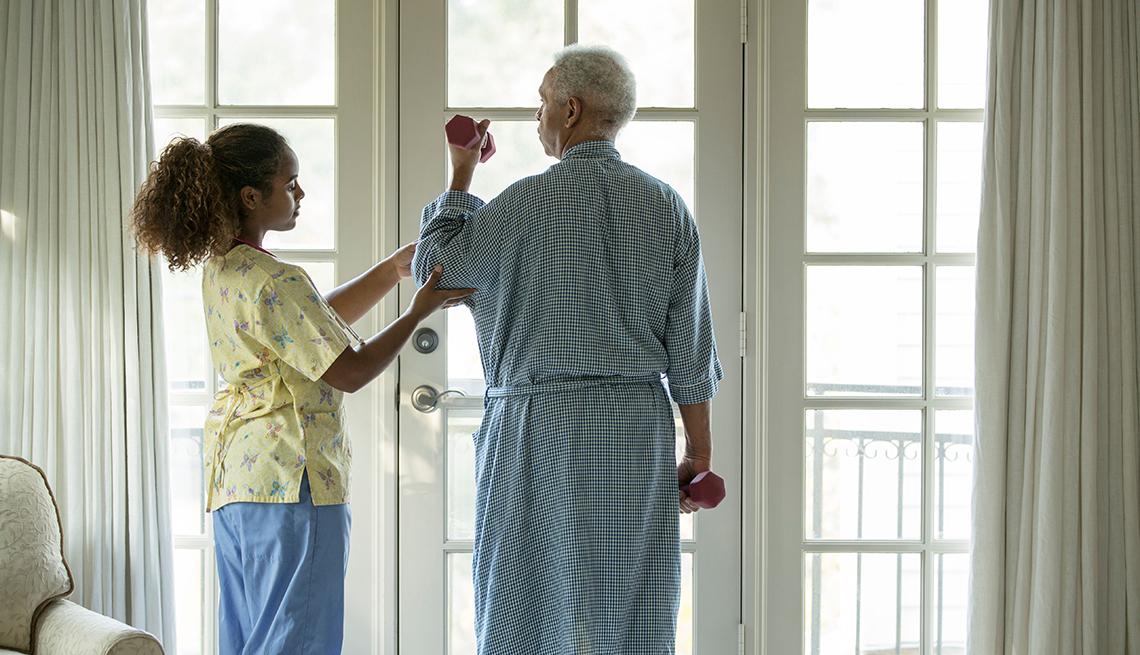 Fisioterapista joven ayudando a un hombre mayor con su rutina