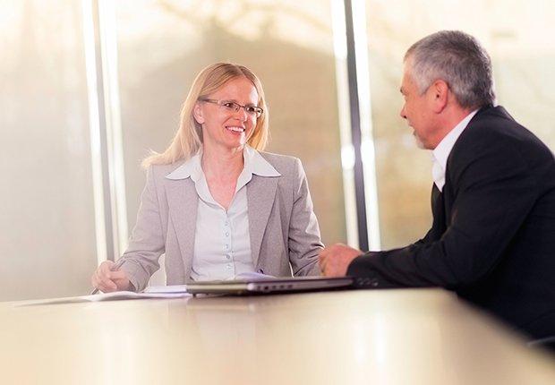Mujer en una sala de juntas recibiendo la asesoría de un hombre
