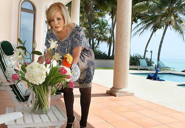 Mujer acomodando unas flores sobre una mesa en una casa con piscina frente a la playa