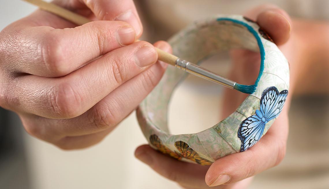 Manos pintando una pulsera