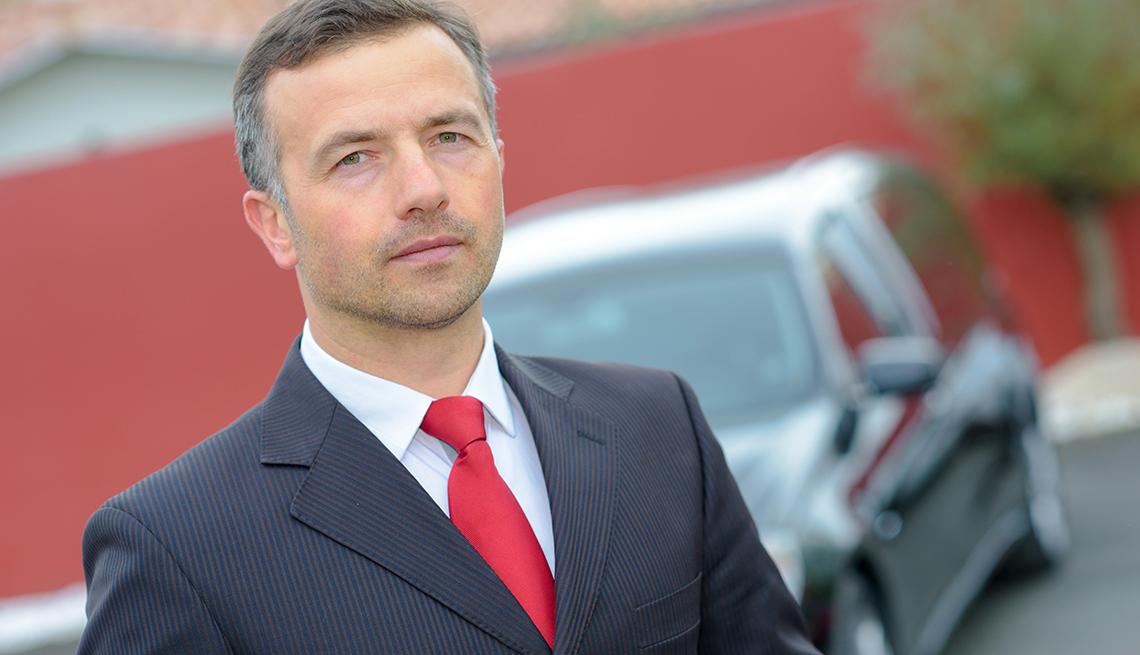 Hombre usando un traje de corbata frente a un carro funerario - Empleos con un salario anual superior a los 100 mil dólares