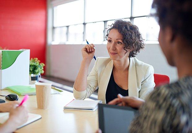 Mujer en una sala de juntas iluminada con luz natural - Empleos con un salario anual superior a los 100 mil dólares