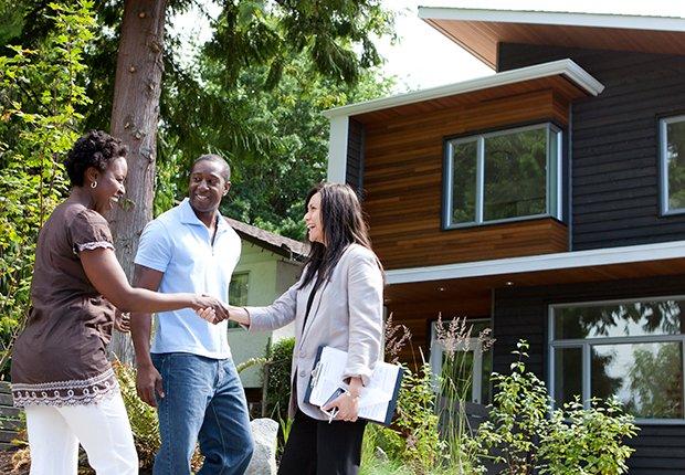 Pareja con una mujer frente a una casa - Empleos con un salario anual superior a los 100 mil dólares