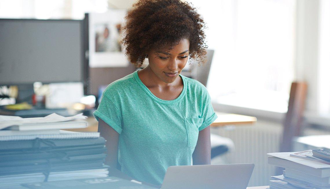 Mujer en una oficina frente a una computadora personal