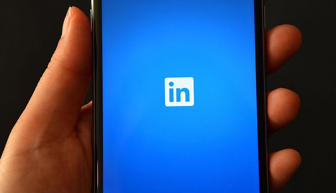 Person holding smartphone showing Linkedin logo, Job Seekers,