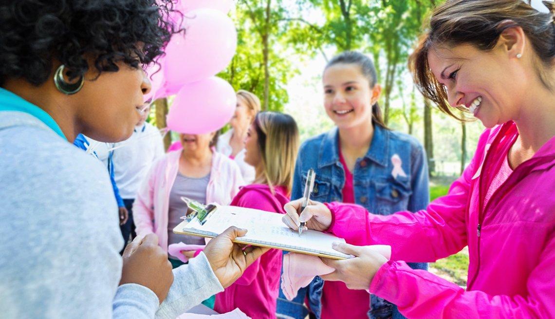 Mujeres en un parque mientras una firma una factura