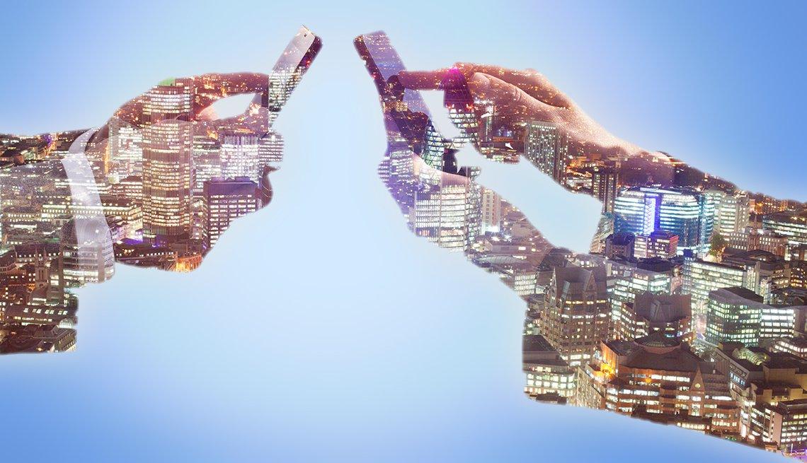 Paisaje de una ciudad recortado sobre manos de dos personas tocando teléfonos móviles