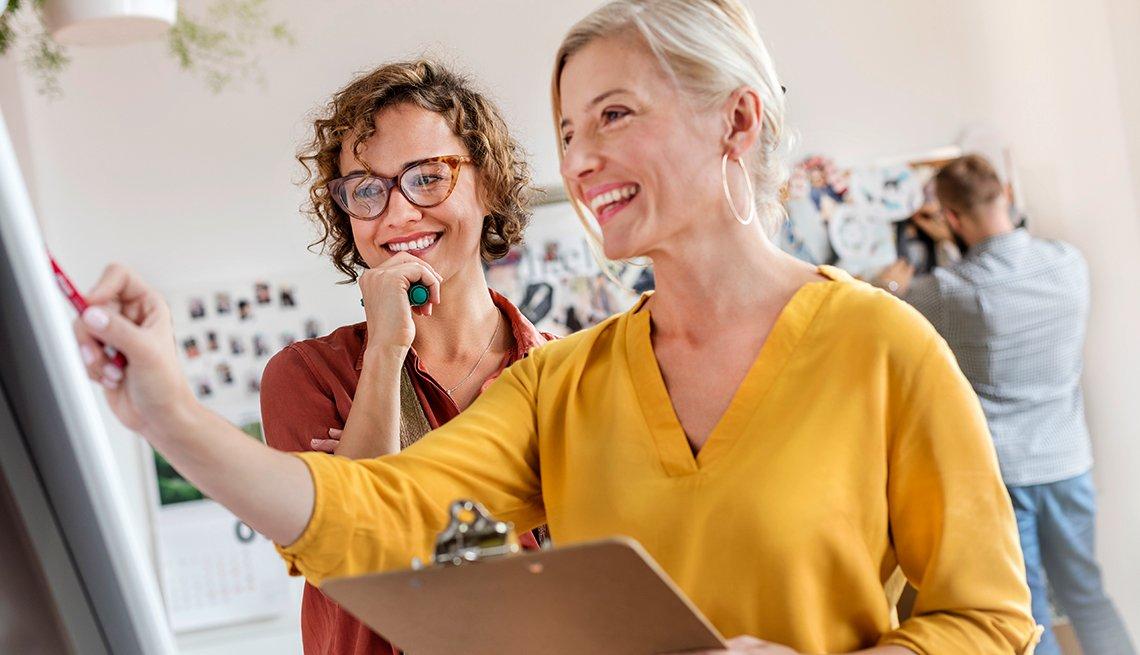 Dos mujeres sonriendo y mirando una pizarra