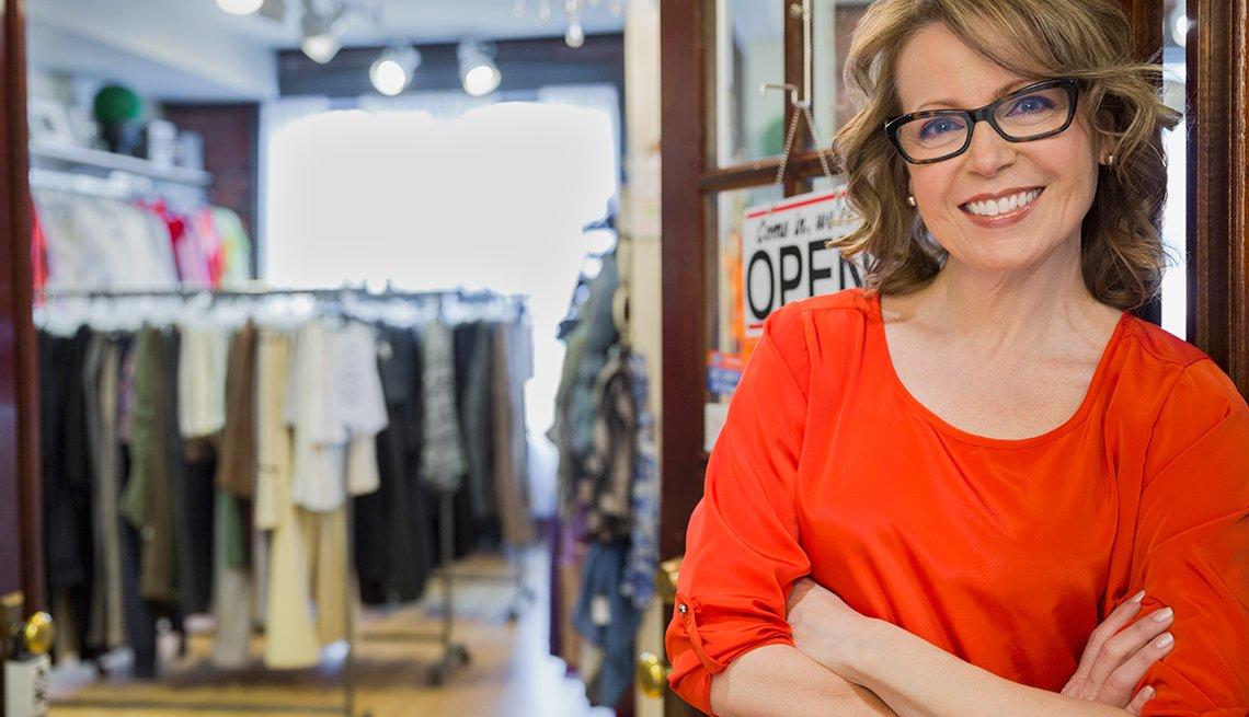 Mujer sonriente a la entrada de un almacén de ropa
