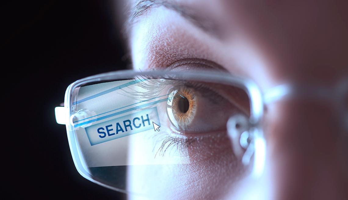 Ojo con un lente de lectura que refleja una pantalla que dice búsqueda en inglés