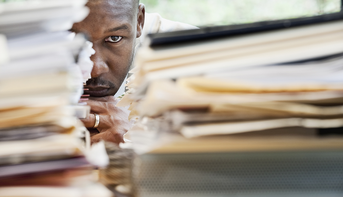 Frustrated Man At Work Sits Behind Piles Of Work, AARP Work, On The Job, What To Do If You Are Bullied At Work