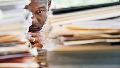 Intimidado en el trabajo - El hombre se enfrenta el trabajo abrumador.