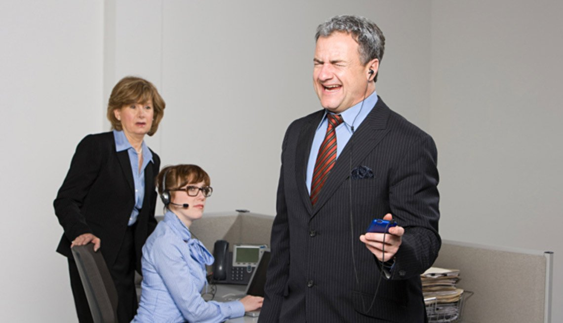 Businessman listening to MP3 player, tips on office etiquette