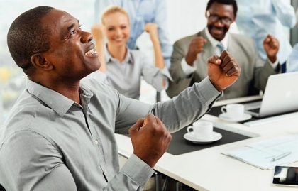 Hombre con las manos empuñadas y mirnado hacia arriba, en señal de felicidad - 5 pasos para enamorarse de nuevo de su trabajo