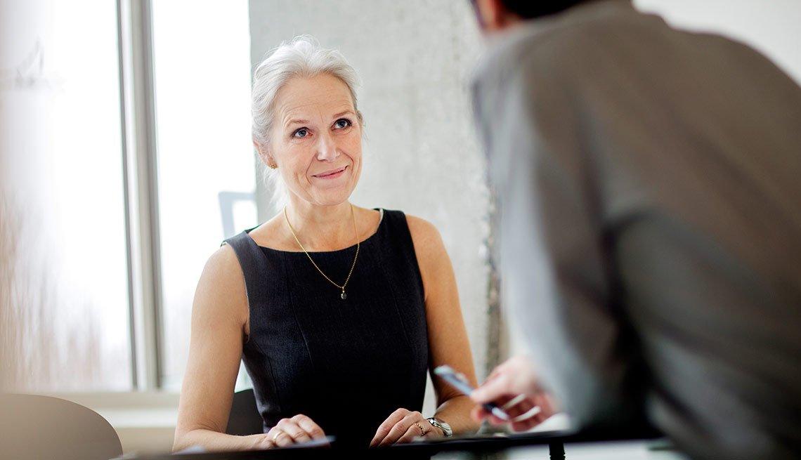 Mujer mayor habando con otra persona en una oficina