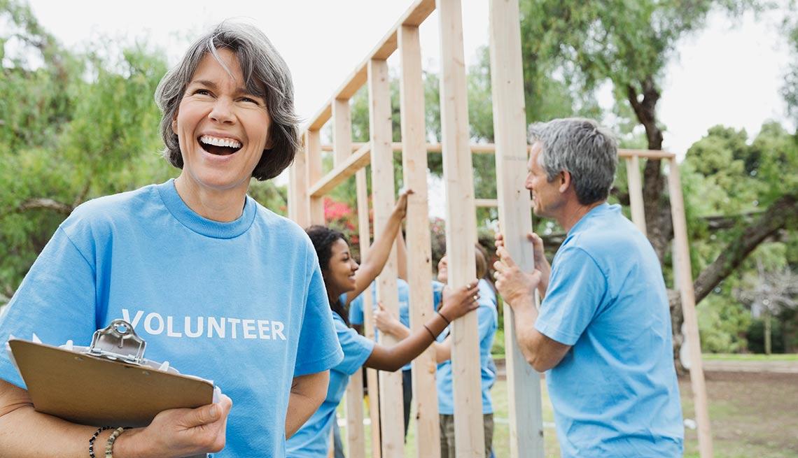 item 4 of Gallery image - Mujer sonriendo con una camisa azul que dice voluntaria frente a otras personas que construyen una vivienda