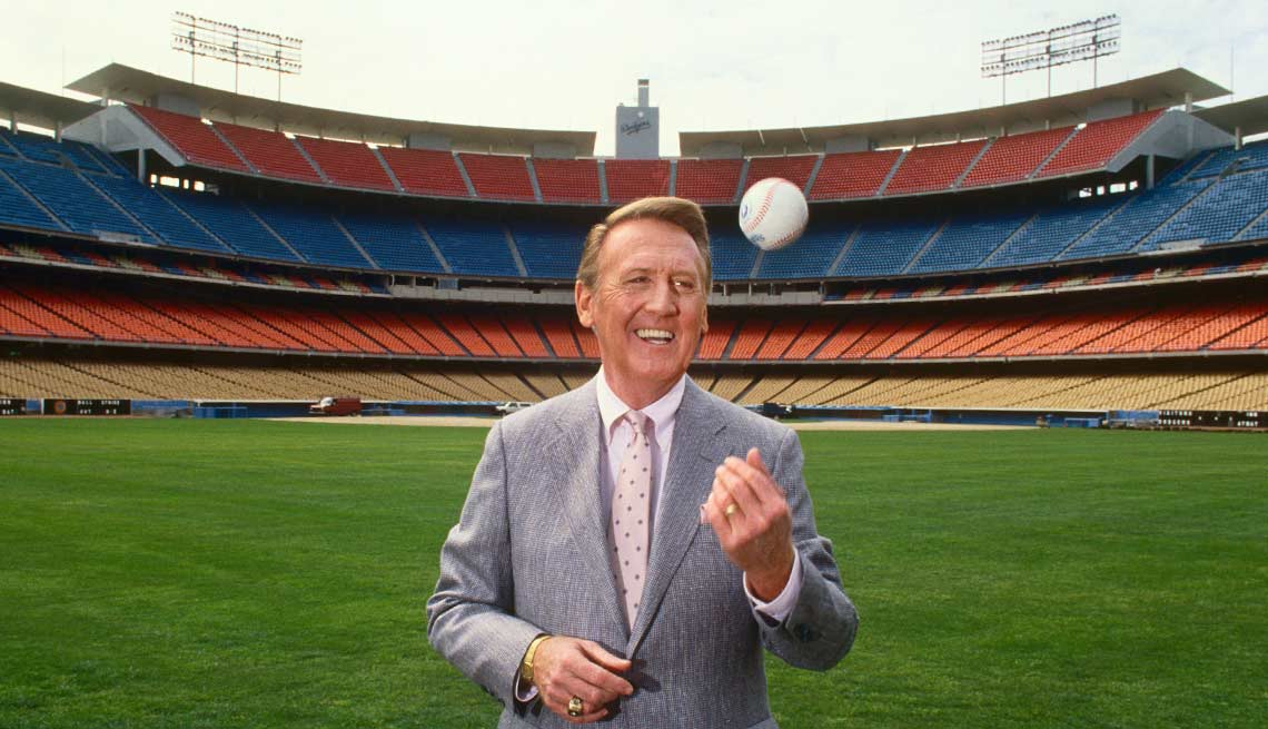 Voice of the Los Angeles Dodgers radio broadcasts, Vin Scully, poses in the outfield of Dodger Stadium during a 1990 Los Angeles, California.