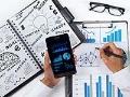 Manos de un hombre con un teléfono, calculadora, cuaderno de apuntes y agenda - Organiza tu tiempo en el trabajo