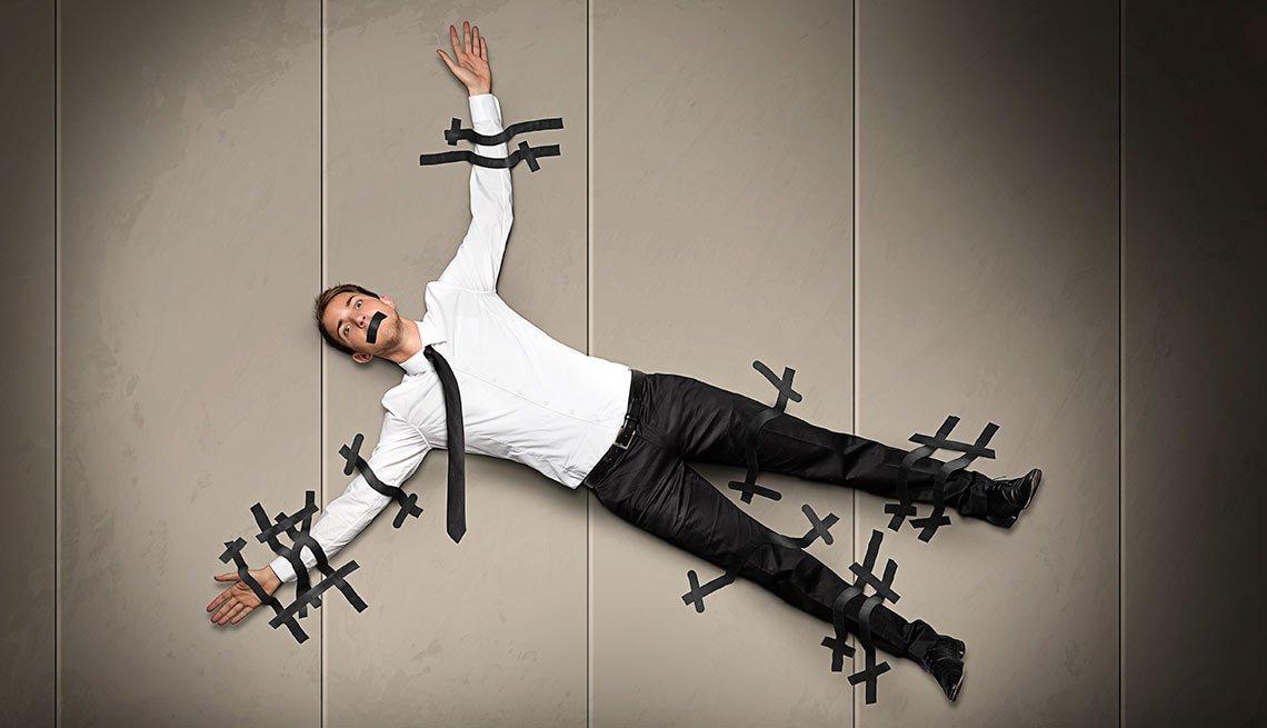 hombre pegado a una pared con cintas