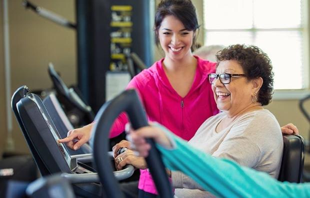 Mujer mayor sentada en una bicicleta estática y asistida por una mujer más joven - Beneficios del empleador que podrían ahorrarte dinero
