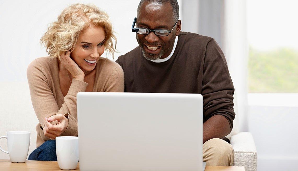Mujer y hombre viendo una computadora personal encima de una mesa de sala