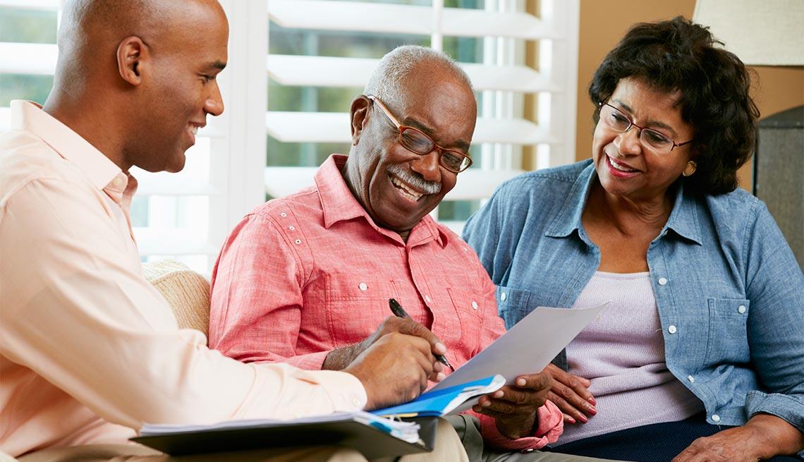 Un asesor financiero dando una asesoría a una pareja mayor en su hogar