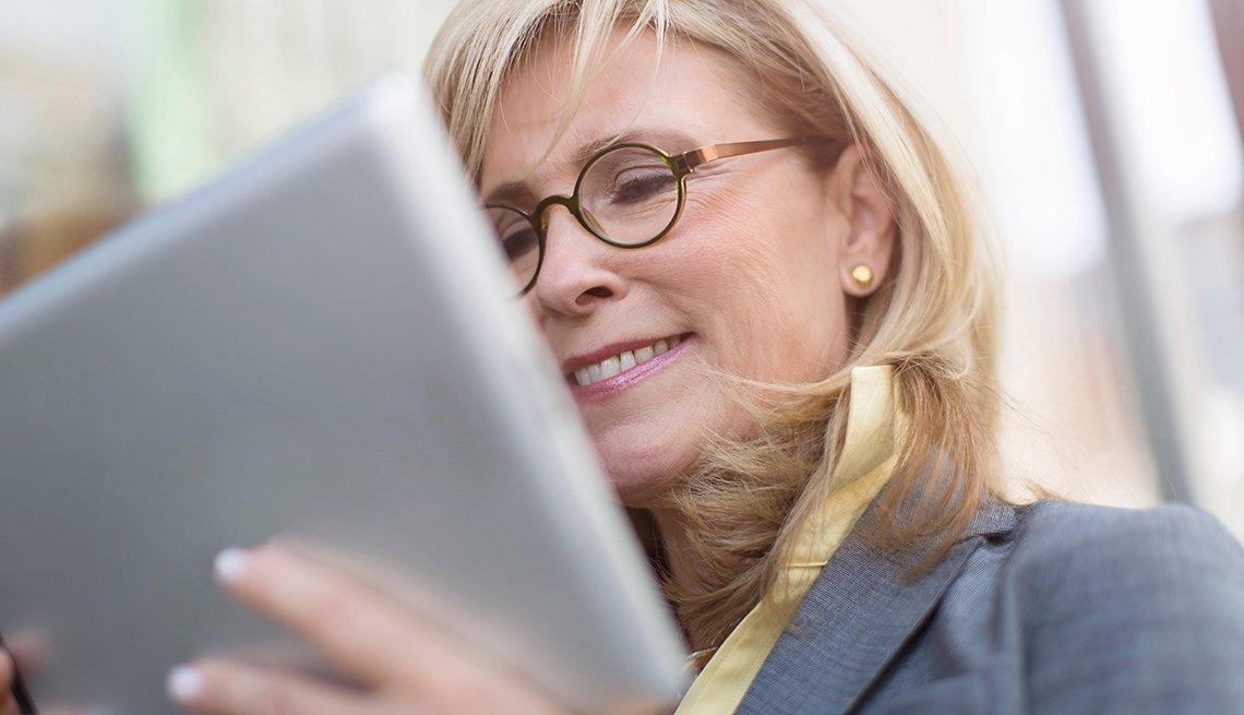 Mujer mirando una tableta para ver herramientas tecnológicas que te hacen más productivo