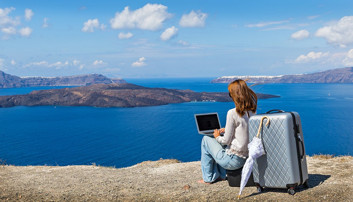 a woman works on her travel business by the sea