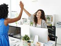 Dos mujeres chocando sus manos en señal de victoria, como cuando tienes un trabajo compartido