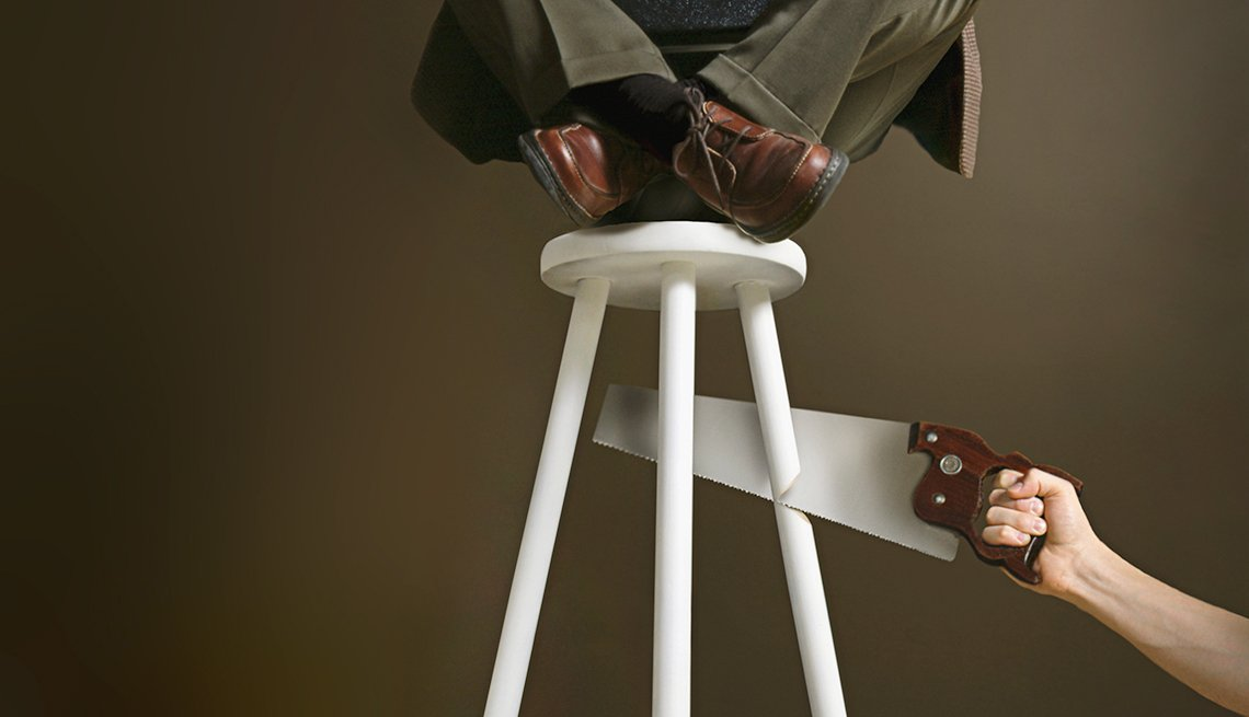 Pies de un hombre vestido de traje y sentado sobre un banco, al cual se le está cortando una pata con un serrucho.