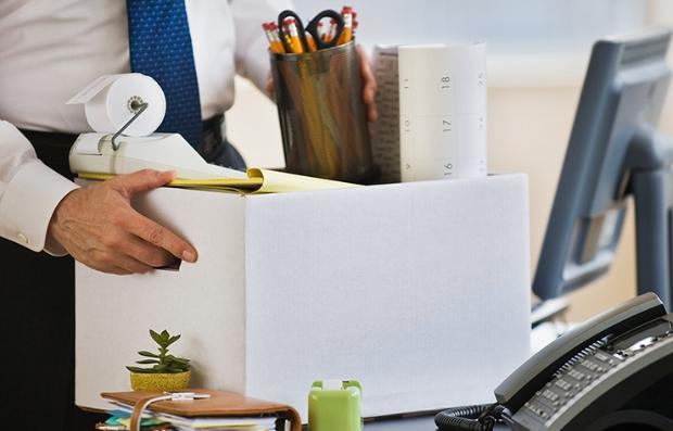 Manos de un hombre vestido con traje recogiendo sus objectos personales de un escritorio. Conoce tus derechos si eres despedido de tu trabajo.