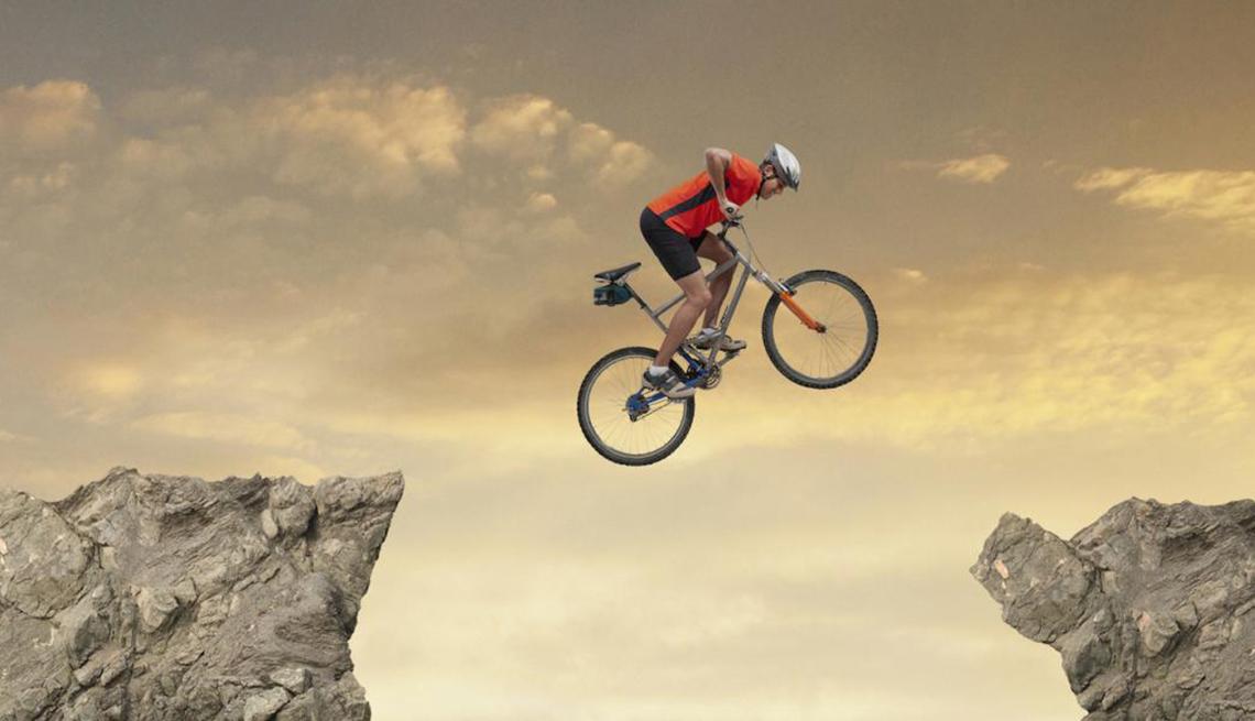 Man on Bicycle Jumping Between Rocks