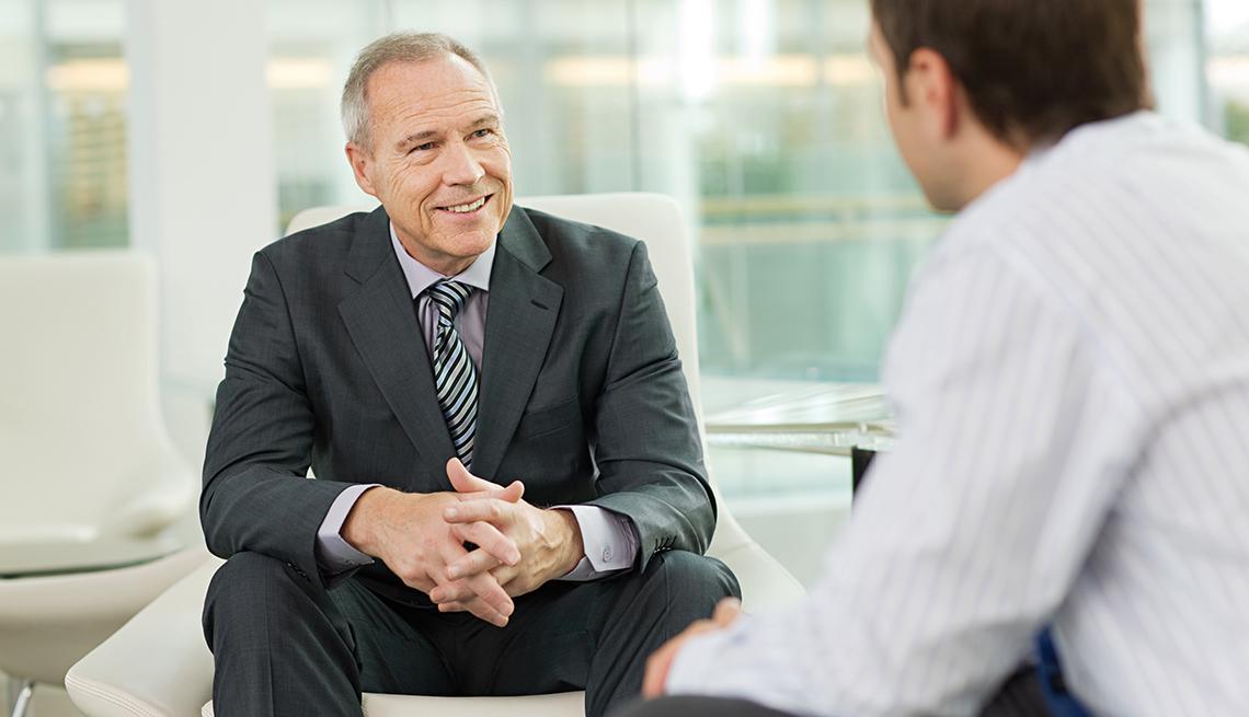 Hombre de negocios sentado conversando con su jefe mas joven - Se feliz en tu trabajo