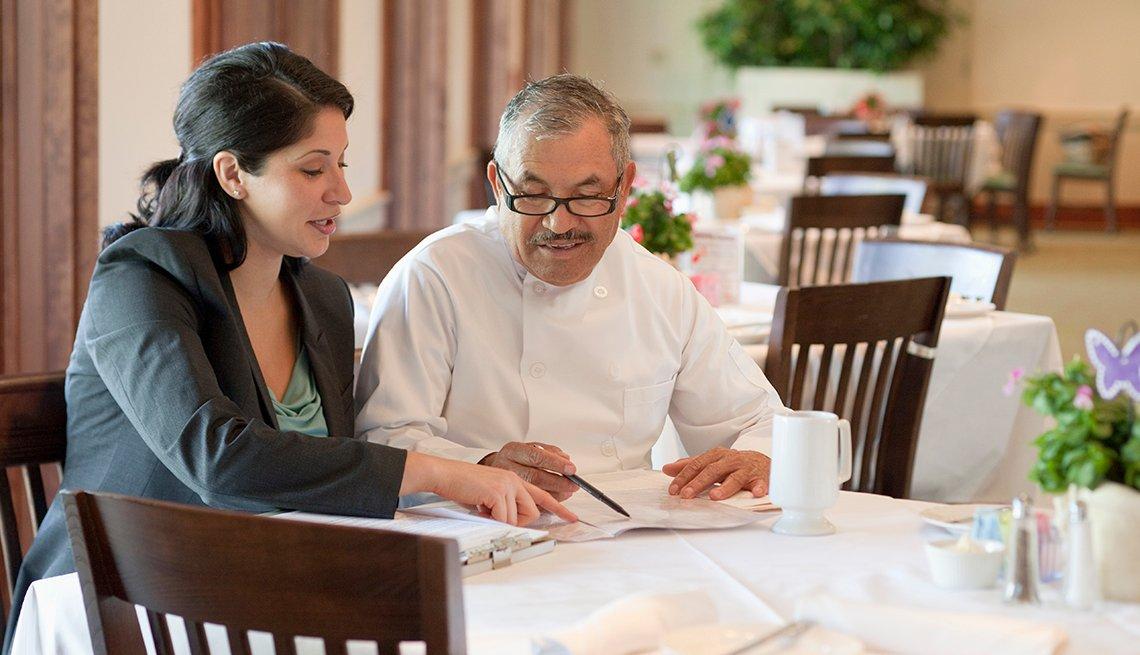 Ejecutiva analizando unos papeles con un chef en un restaurante, debes tener un plan de mercado.