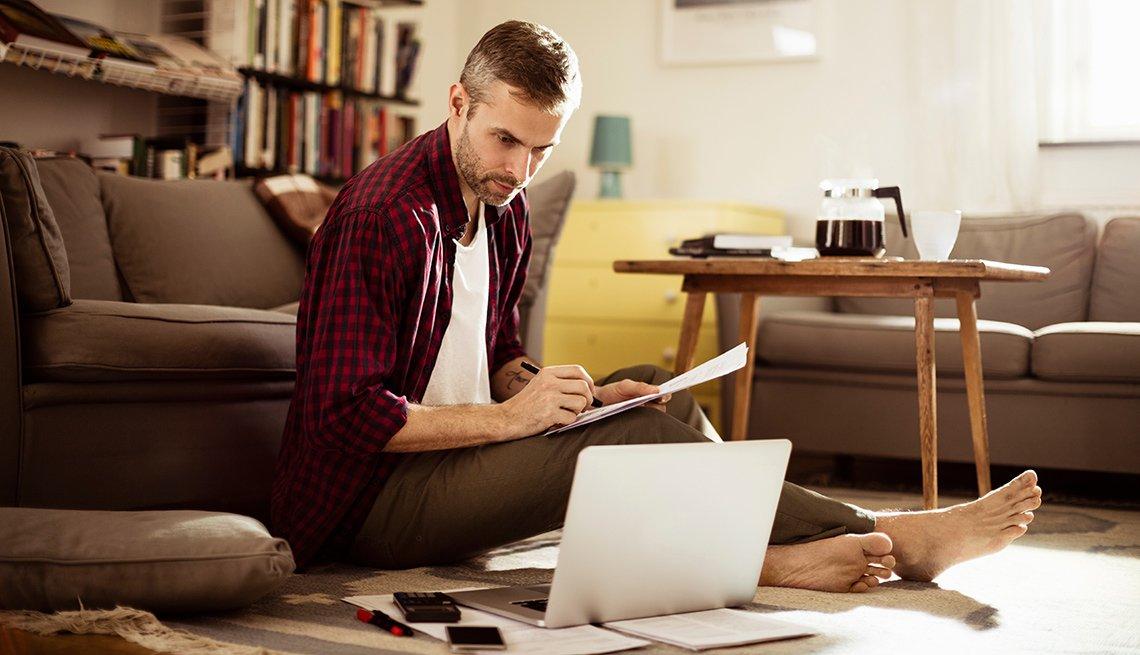 Hombre con papeles y computadora en la sala de su casa