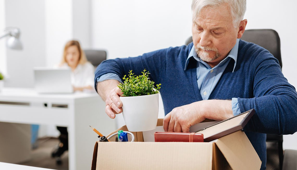 Older office manager sitting in the office and gathering his belongings while holding the box and expressing despair