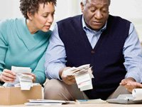Couple reviewing bills - both husband and wife need to know how to manage family money