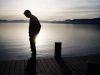 El hombre en el muelle con una puesta de sol simboliza los problemas de dinero de la jubilación