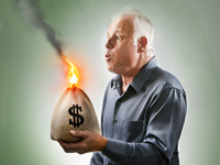 Image of man holding a burning bag of money. What to do with your money when stock market values drop.