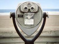 Calculadora para la jubiilación de AARP - Binoculares con océano al fondo.