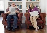 Boomer couple in armchairs split between work and retirement
