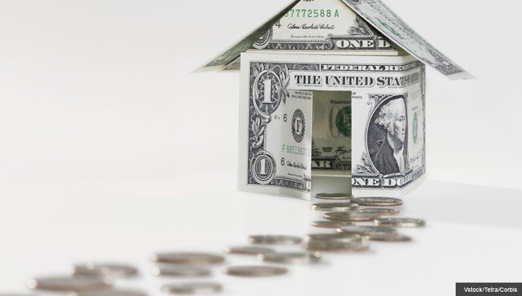Monedas hacen un camino que los lleva a una casa hecha con un dólar
