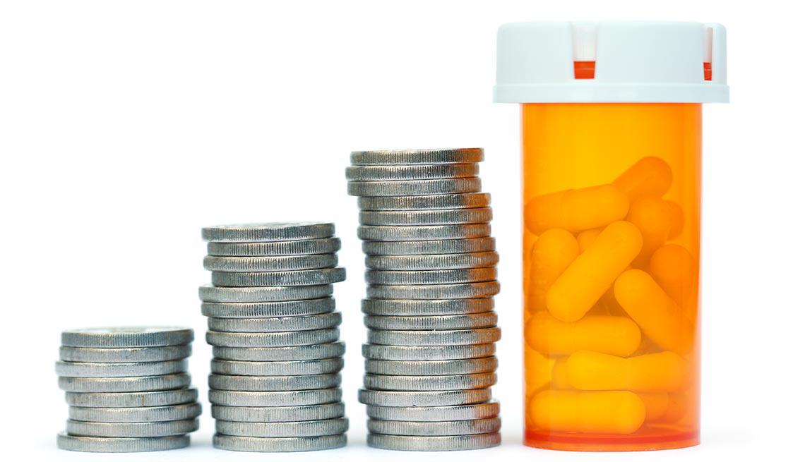 Monedas apiladas y botella de pastillas