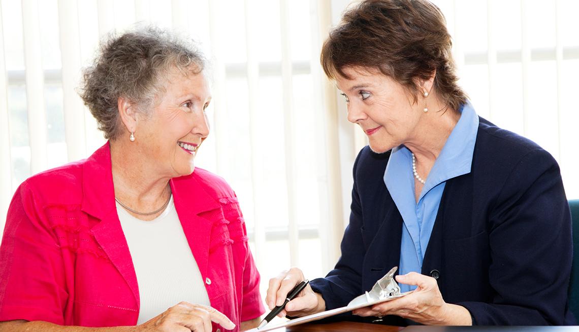 Mujeres mayores hablando de un contrato.