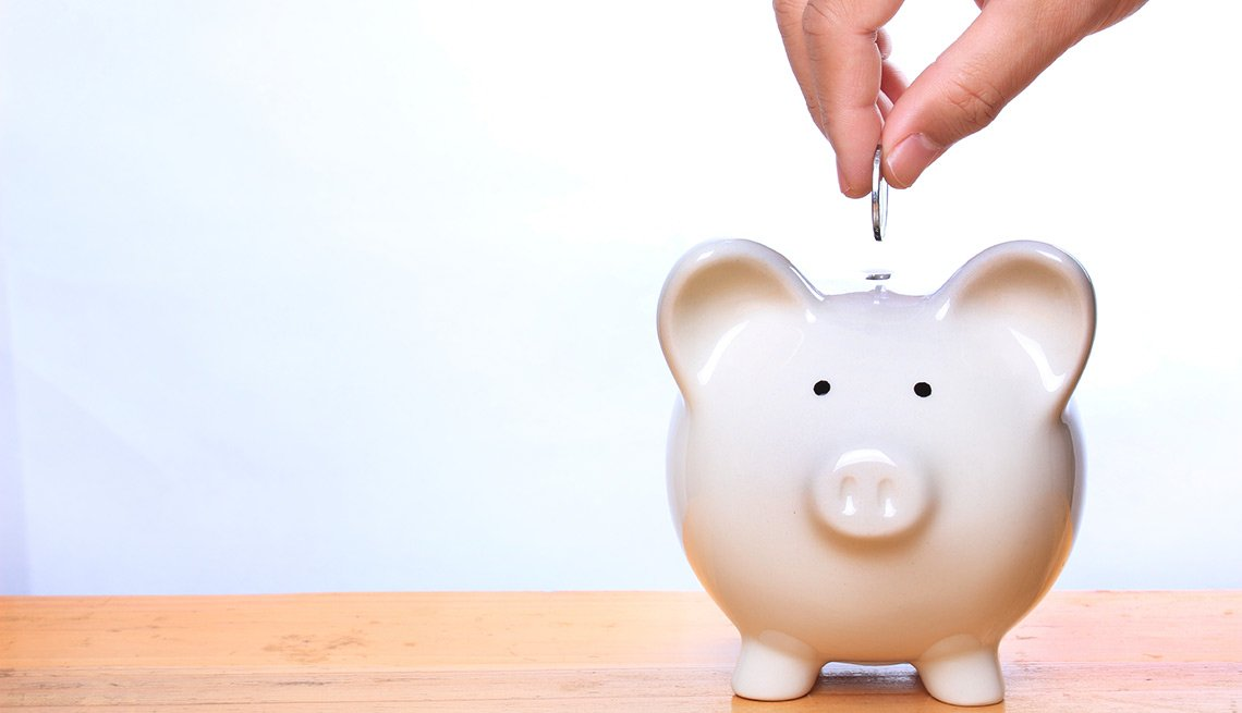 Mano colocando una moneda en una alcancía - Seguro Social ayuda a los cónyuges