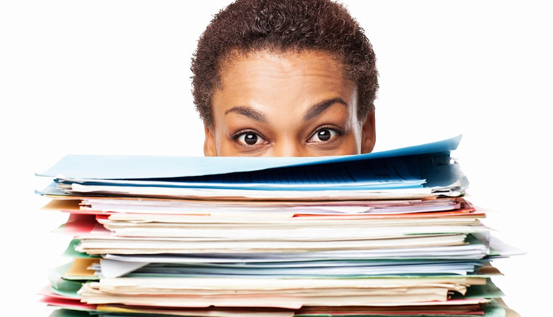 Mujer detrás viendo al frente através de documentos apilados - Seguro Social ayuda a los cónyuges