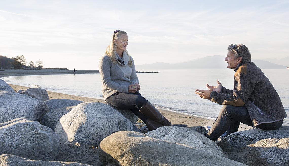 Pareja mayor sentada en unas piedras frente a una playa - Formas para realinear tu jubilación en pareja