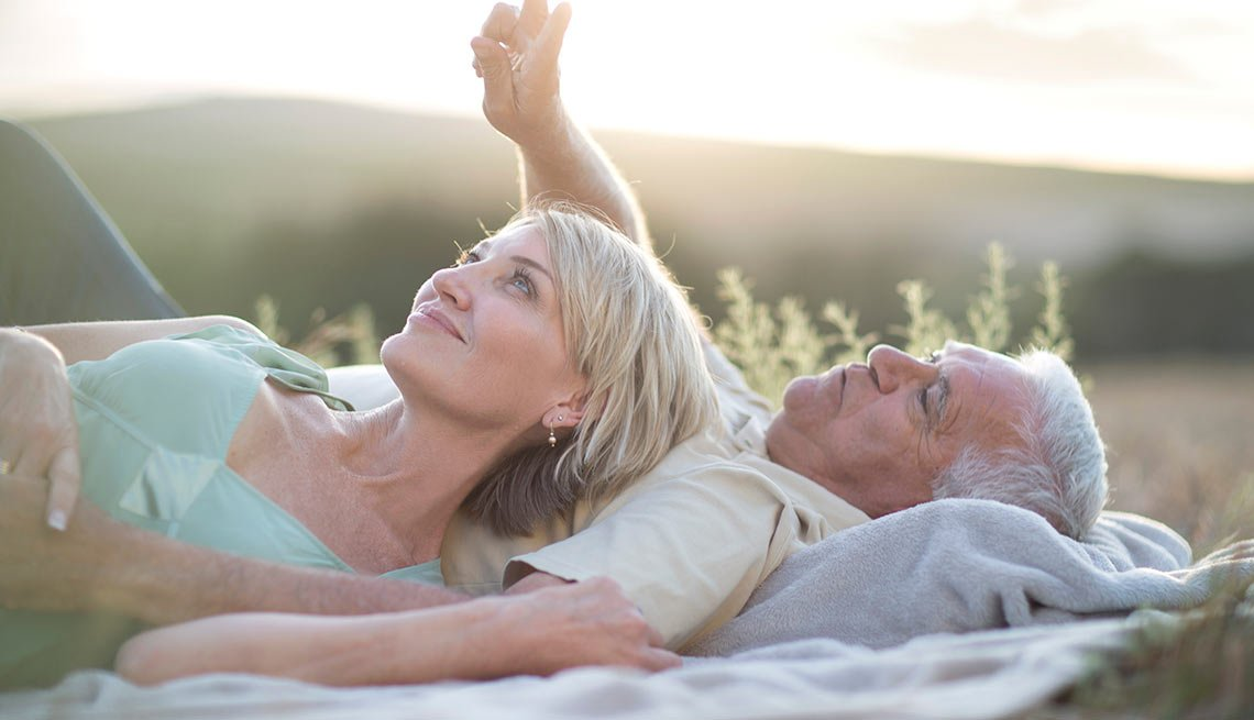 Pareja mayor acostada en un sábana en un bosque - Formas para realinear tu jubilación en pareja